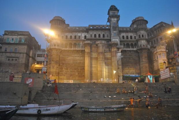 Illuminated buildings along the Ganges in Varanasi before sunrise