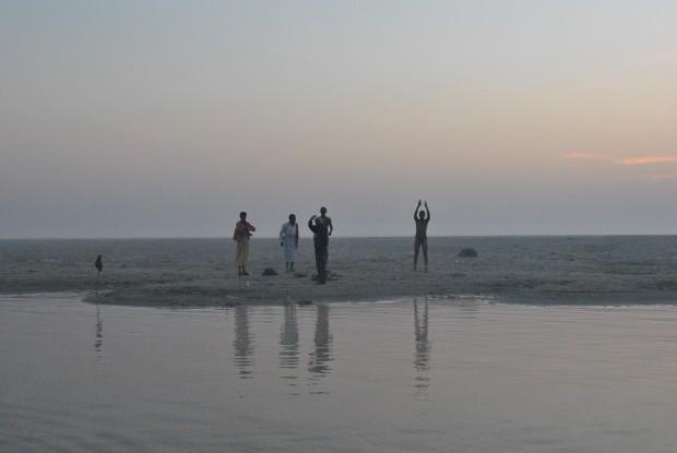 People on a sandbank in the Ganga in Varanasi before sunrise