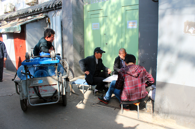 A group of men in a Hutong is chatting and playing games in the streets