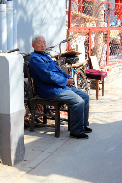 An elderly man is watching life go by