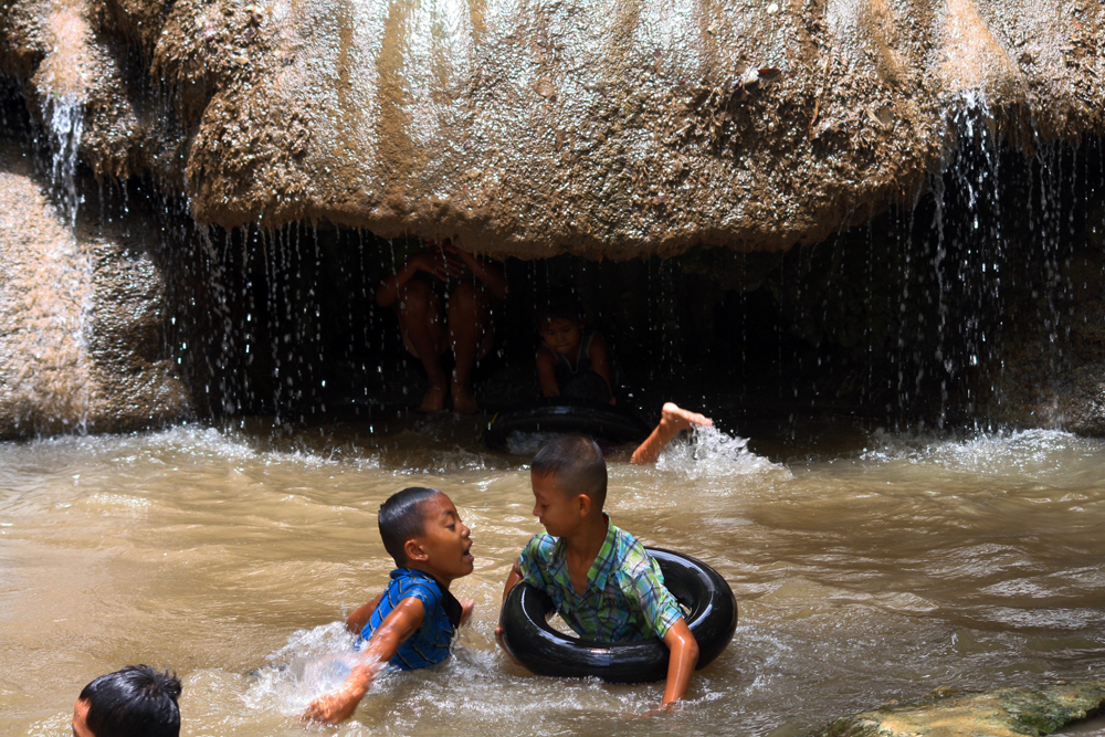 Locals taking a bath at the Sai Yok Noi Waterfall Kanchanaburi Thailand Asia
