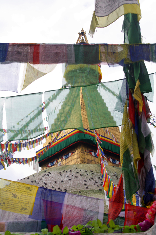Travel bloggers tips for Bhutan - Bodnath Stupa in Kathmandu behind prayer flags in August 2010
