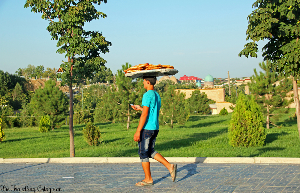 The Jewels of Samarkand - Tradition and modernity - Bread vendour with smartphone